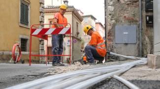 COLMARE IL DIVARIO CON L'EUROPA A sinistra, operai al lavoro per passare nei pozzetti i nuovi cavi necessari per garantire la banda ultra larga. L'Italia risulta fra i Paesi Ue più indietro rispetto alla diffusione di questa tecnologia