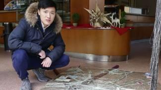 Uno dei fratelli Yang mostra la vetrata spaccata del bar-pizzeria Attalmi