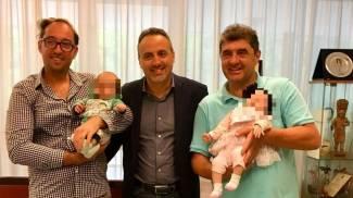 I gemellini in braccio ai due papà e il sindaco di Gabicce Domenico Pascuzzi