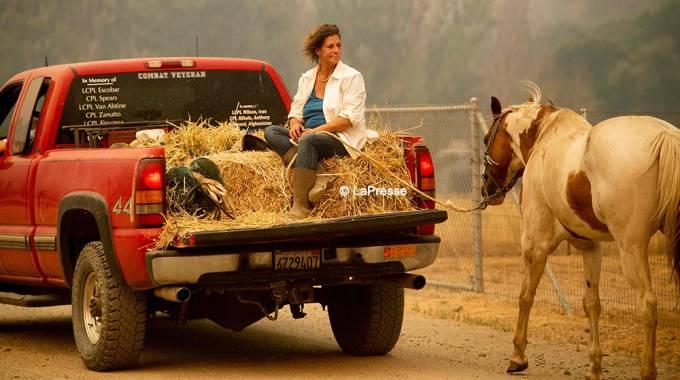 Debbie Prior e il suo cavallo lasciano la propria abitazione a casua del Ranch Fire