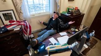 Un assalitore del Congresso si siede alla scrivania di Nancy Pelosi (Ansa)