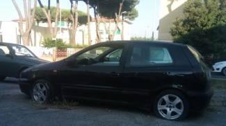 Un'auto abbandonata da qualche tempo con gomme a terra