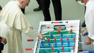 papa Francesco gioca a biliardino durante l'udienza generale (Ansa)