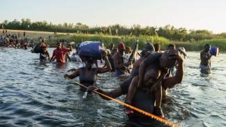 Un gruppo di migranti haitiani mentre attraversa il Rio Grande (Ansa)